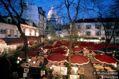 Paris, Montmartre, Place du Tertre, a pavement cafe lit up at night, Sacré Coeur in the distance