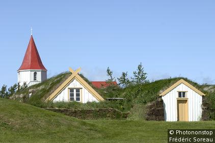 Islande, environs de Varmahlid, ferme de Glaumbaer recouverte de gazon, clocher en arrière-plan