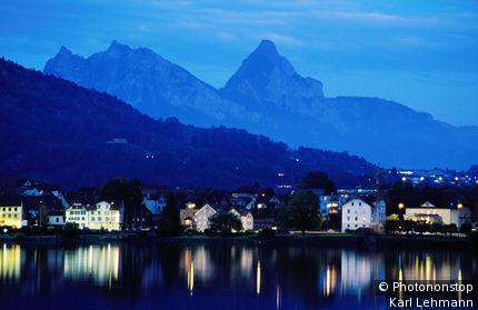 Switzerland, Zug, Arth, Arth town reflected in Zugersee (Lake Zug) at dusk, Mythen peak in background.