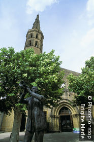 Marciac, église sur place avec arbres verdoyants, statue d'un trompettiste, panneau festival de jazz au fond