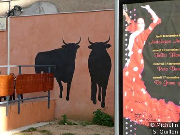 Terrasse de bar avec peinture de taureau sur le mur et affiche pour spectacle de flamenco