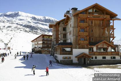 L'Alpe d'Huez, 2 chalets au pied des pistes, montagne en arrière-plan, ciel bleu