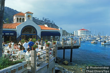 Tourists on restaurant balcony with Casino and yachts at Avalon Bay on Catalina Island off Southern California,USA