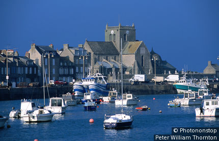 France, Normandy, Barfleur, Boats in harbour with church behind.