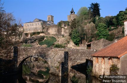 Stone bridge across river Thouet with old town ramparts in background. Parthenay, Poitou-Charentes, France