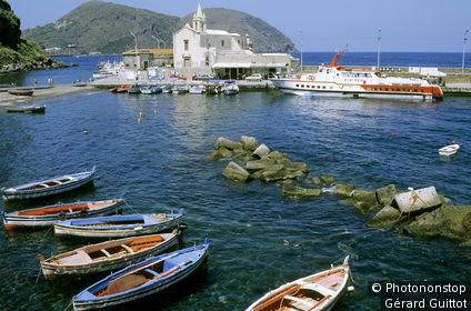 Italie, Sicile, iles Eoliennes, Lipari, barques amarrées au 1er plan, église en arrière plan, bateau le long du quai