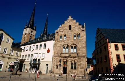 Romanesque Marktapotheke (pharmacy) with twin-towers of Johanneskirche behind in town centre. Saalfeld, Thuringia, Germany