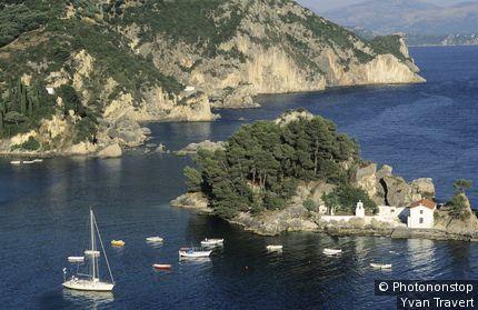 Vue plongeante sur maison sur îlot verdoyant et bord de mer.