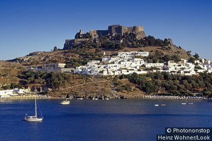 View at the town Lindos and the acropolis under blue sky.