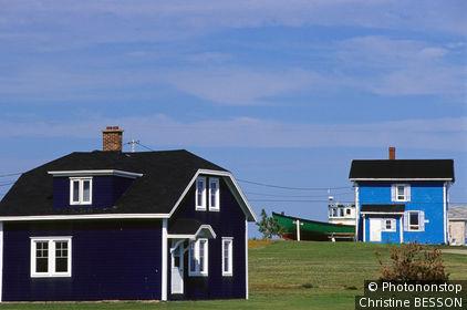 Province du Québec, Iles de la Madeleine, Ile du cap aux Meules, 2 maisons en bois bleu marine et bleu turquoise, dans verdure, barque au fond