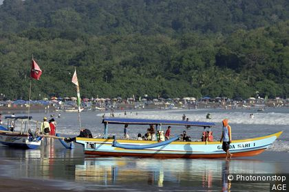 Local fishermen turned tourist operators on busy weekends at popular Pantai Barat. Pangandaran, West Java,Java, Indonesia