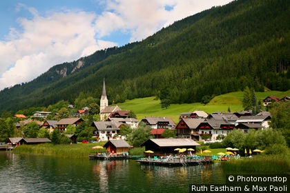Austria, Carinthia, Spittal an der Drau, Mountain houses and sun decks with umbrellas on shores of lake Weissensee, in Gatschach village.