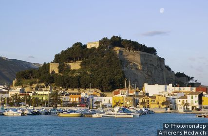 Spain, Alicante Province, Denia, marina, fort and waterfront with moon