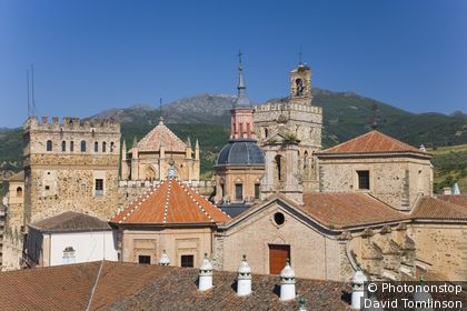 Towers of Royal Monastery of Santa Maria de Guadalupe with parador roof in foreground.