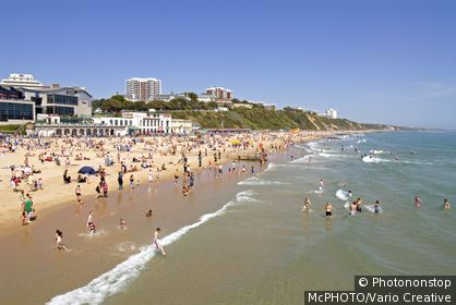 Image of locals and tourists at the wellknown popular beachside resort of Bournemouth in East Sussex, South England.