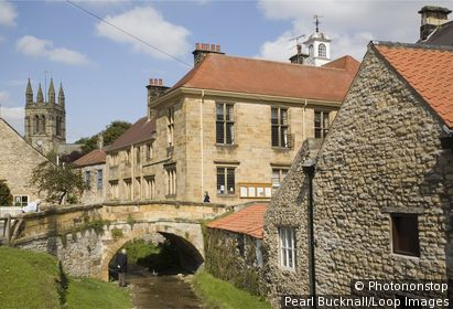 England, North Yorkshire, Helmsley. Town Hall, All Saints Church tower and stone bridge over stream in village on edge of North York Moors National Park.