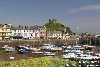 England, Devon, Ilfracombe. Boats moored in Ilfracombe with St Nicholas's Chapel in the background. Ilfracombe dates back to the Iron Age and its name is translated from the 'Valley of the sons of Alfred'.