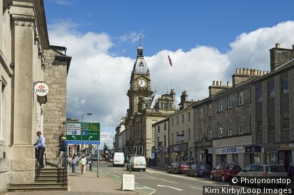 England, Cumbria, Kendal. A view along Highgate in Kendal, past shops and banks towards the Town hall.