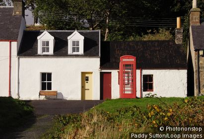 Scotland, Highland, Kyle of Lochalsh. Red telephone box with cottages in the village of Plockton. The village has National Trust conservation status.