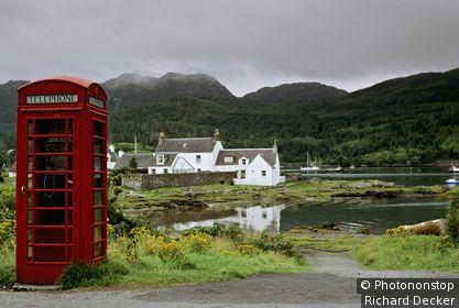 Ecosse, Highlands, Plockton, cabine téléphonique au bord d'une route, lac et colline en arrière-plan