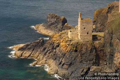 England, Cornwall, St Just. Waves crash below Crowns Head mine engine house on the North Cornish coastline.