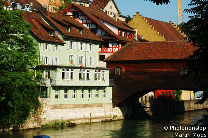 Switzerland, Aargau, Baden, Old town centre with Holzbrücke (wooden bridge) and historic houses along the Limmat River.