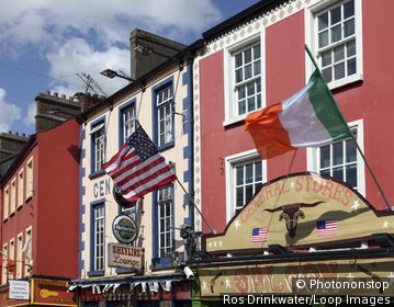 Republic of Ireland, County Monaghan, Carrickmacross. US and Irish flags flying ouside a General Stores in Main Street, Carrickmacross.