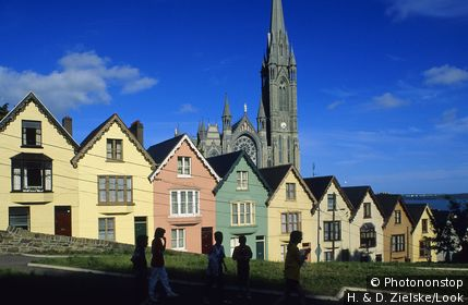 Colourful facades of houses at the Old Town, in the background St. Colman's cathedral, Cobh, County Cork, Ireland, Europe