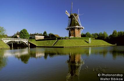 Pays-Bas, Frise, Dokkum, Het Grootdiep, moulin sur tertre verdoyant au bord d'un canal, ciel bleu