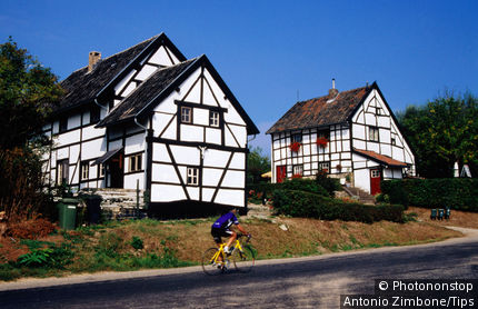 Netherlands, Limburg, Epen, Cyclist passing in front of half-timbered vakwerkhuis.