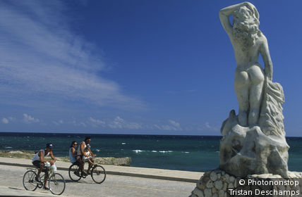 Cuba, Gibara, familles se promenant à vélo sur route en bord de mer, statue d'une femme nue de dos, au 1er plan