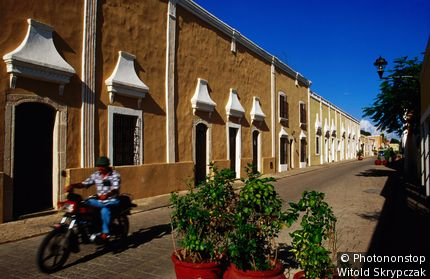 Motorcyclist passing colonial houses on Calle 41A. Valladolid, Yucatan, Mexico