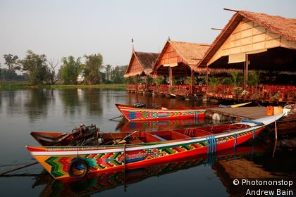 Long-tail boats and restaurants on River Kwai. Khwae Yai River, Kanchanaburi, Thailand