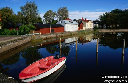 Finland, Scandinavia, Ekenas, Red boat and reflections on the lake.