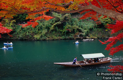 Pleasure boats with tourists being shown Arashiyama's autumn colours.