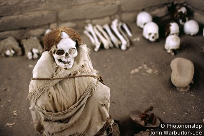 Peru;Nazca;Cemetery of Chauchilla - A Nazca mummy is surrounded by pottery, bone and cloth fragments in the Cemetery of Chauchilla in Peru.