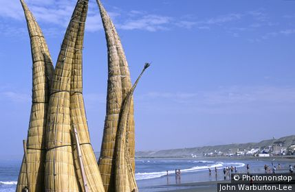 Peru;La Libertad;Huanchaco - Totora (reed) fishing boats are stacked on the beach at Huanchaco, in northern Peru. The boats known as caballitos de totora (little horses of reeds) are the traditional craft of the local pescadores (fishermen).