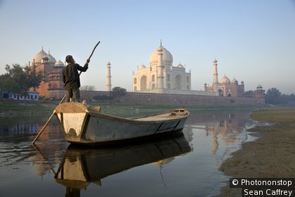 Man poling his boat on the Jamuna River behind the Taj Mahal. Agra, Uttar Pradesh, India