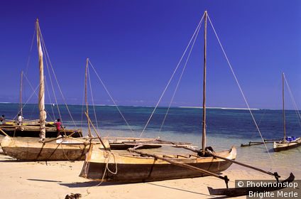 Madagascar, Anakao, pirogues á balanciers sur plage, mer au fond, ciel bleu