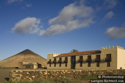 The extinct volcano Montana Oliva behind the historical building Casa de Los Coroneles, La Oliva, Fuerteventura, Canary Islands, Spain, Europe