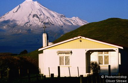 Weatherboard house on Highway 46 heading towards New Plymouth with Mt Taranaki in background. New Plymouth, Taranaki,North Island, New Zealand