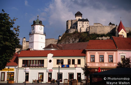 Slovakia, Eastern Europe, Trencin, Old town with gate tower and castle on hill in distance.
