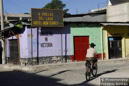 Guatemala, lac Atitlàn, Panajachel, homme à vélo portant un chapeau passant dans une rue aux murs colorés