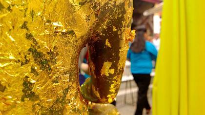 Détail d'un Buddha recouvert de feuilles d'or par les donnateurs